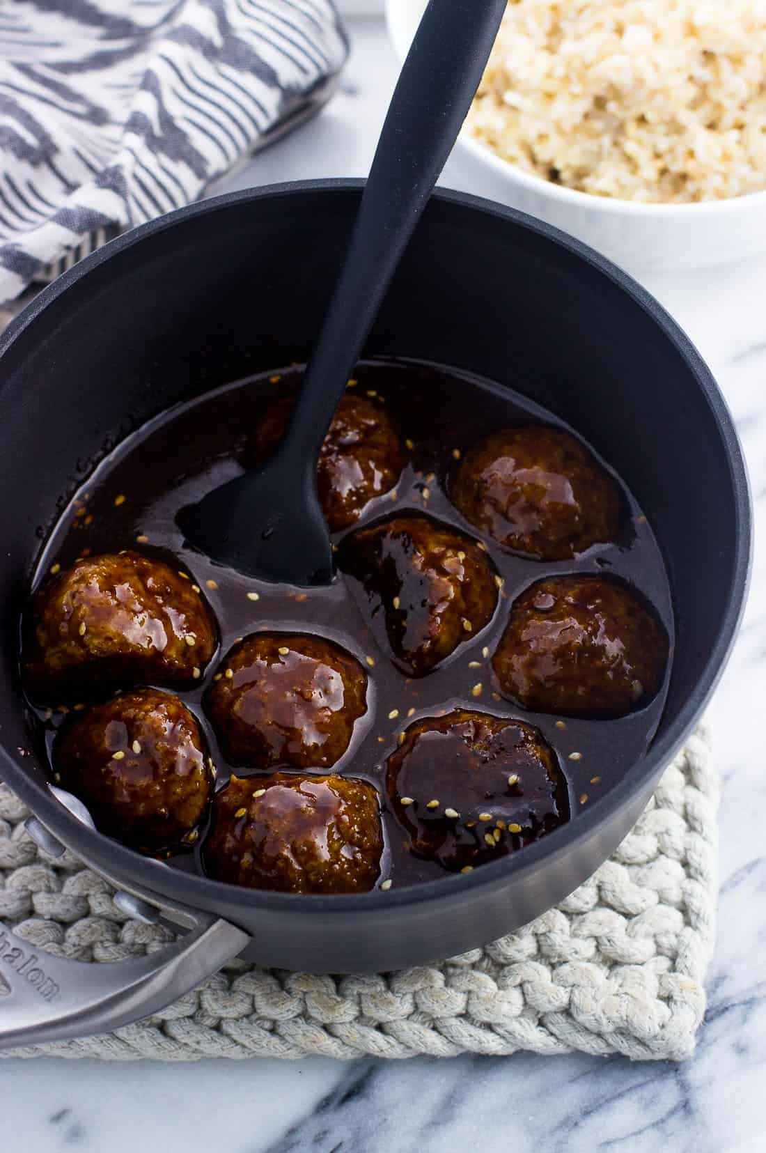 Meatballs in a saucepan covered with hoisin glaze