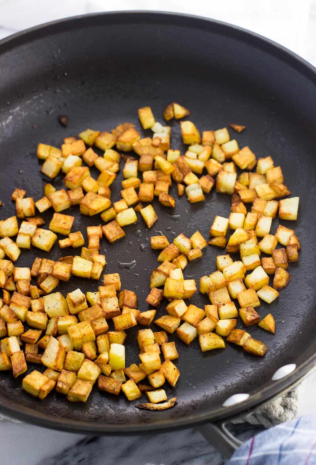 Small cubes of roasted potatoes in a skillet