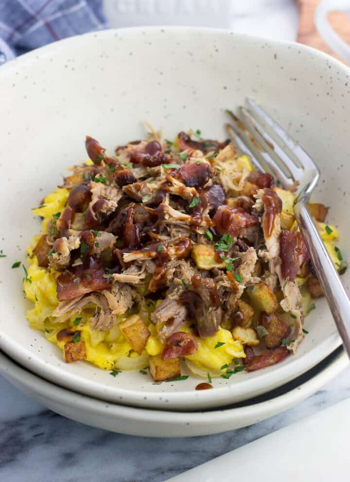 A pile of scrambled eggs, bacon, potatoes, pulled pork, and BBQ sauce in a bowl