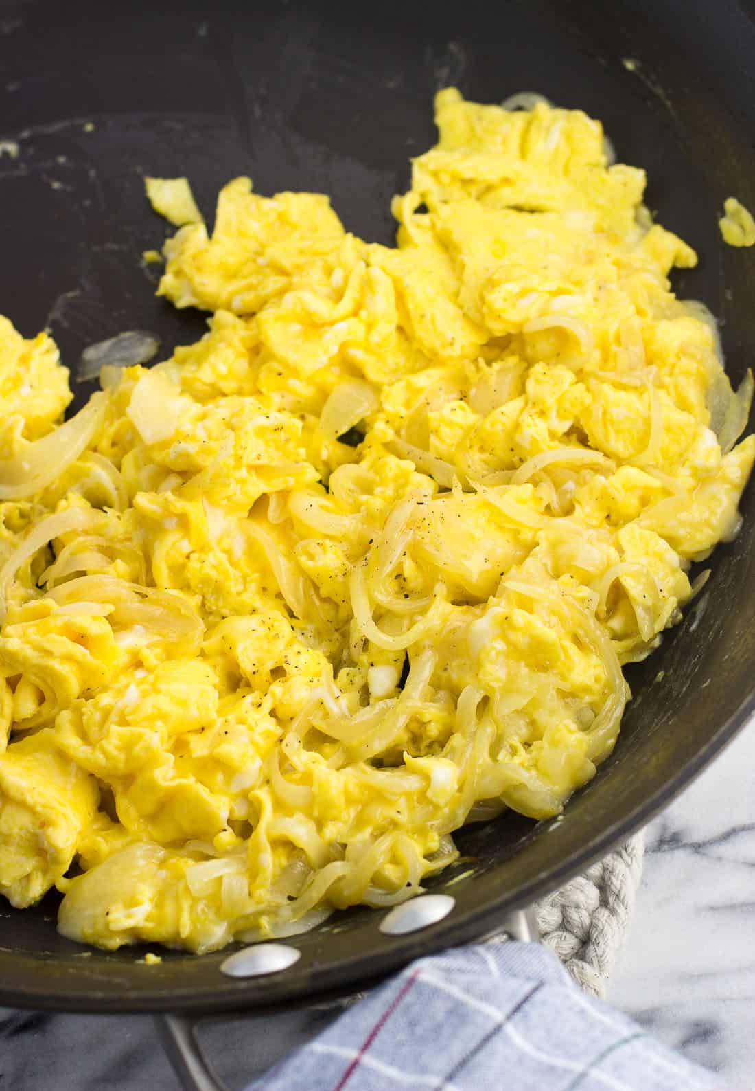 Scrambled eggs mixed with cheese and sauteed onion slices in a skillet