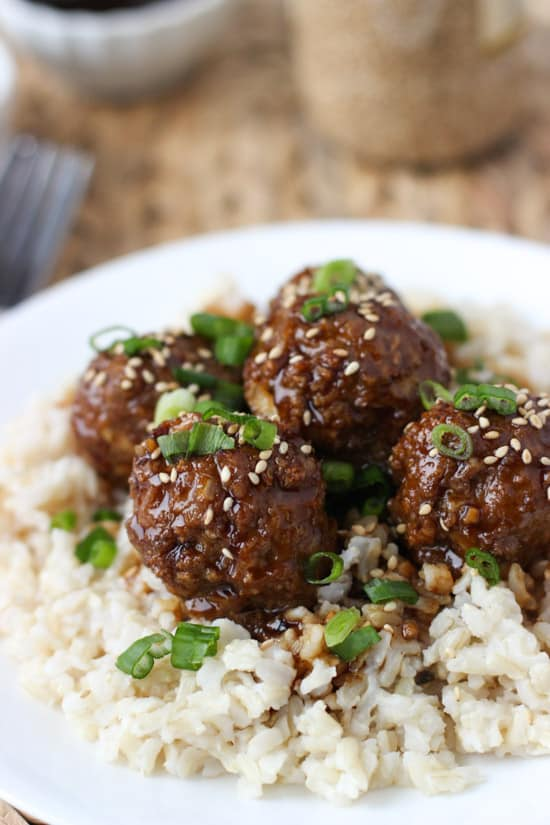 Hoisin meatballs on top of brown rice served on a dinner plate