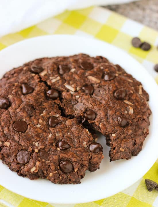 A large chocolate coconut cookie on a dessert plate broken in half.