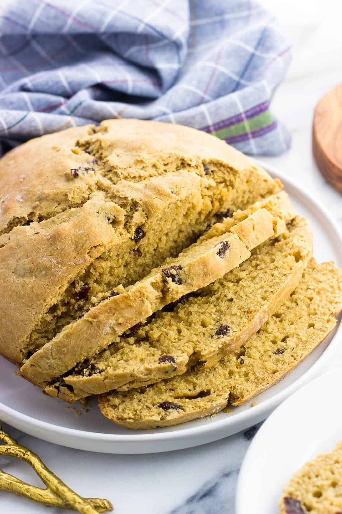 A half-sliced loaf of maple Irish soda bread on a plate