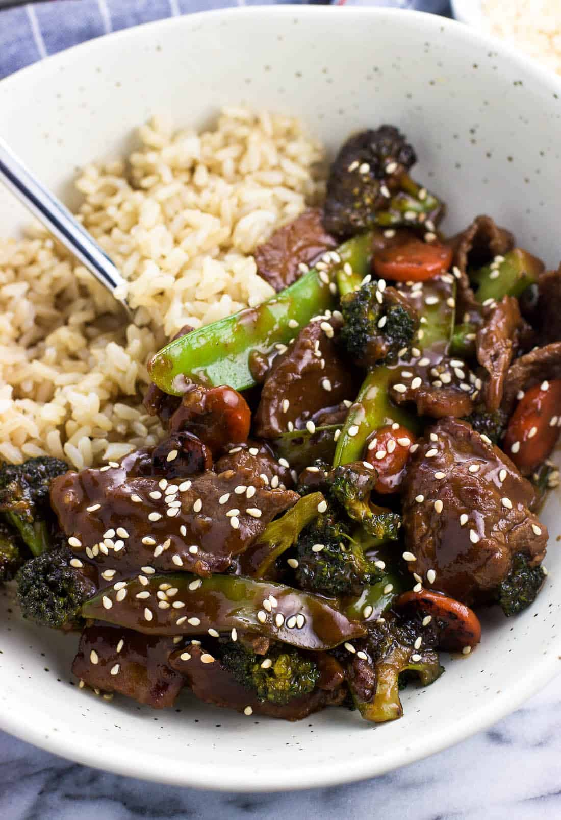 Beef and mixed vegetable stir fry in a bowl served beside brown rice.