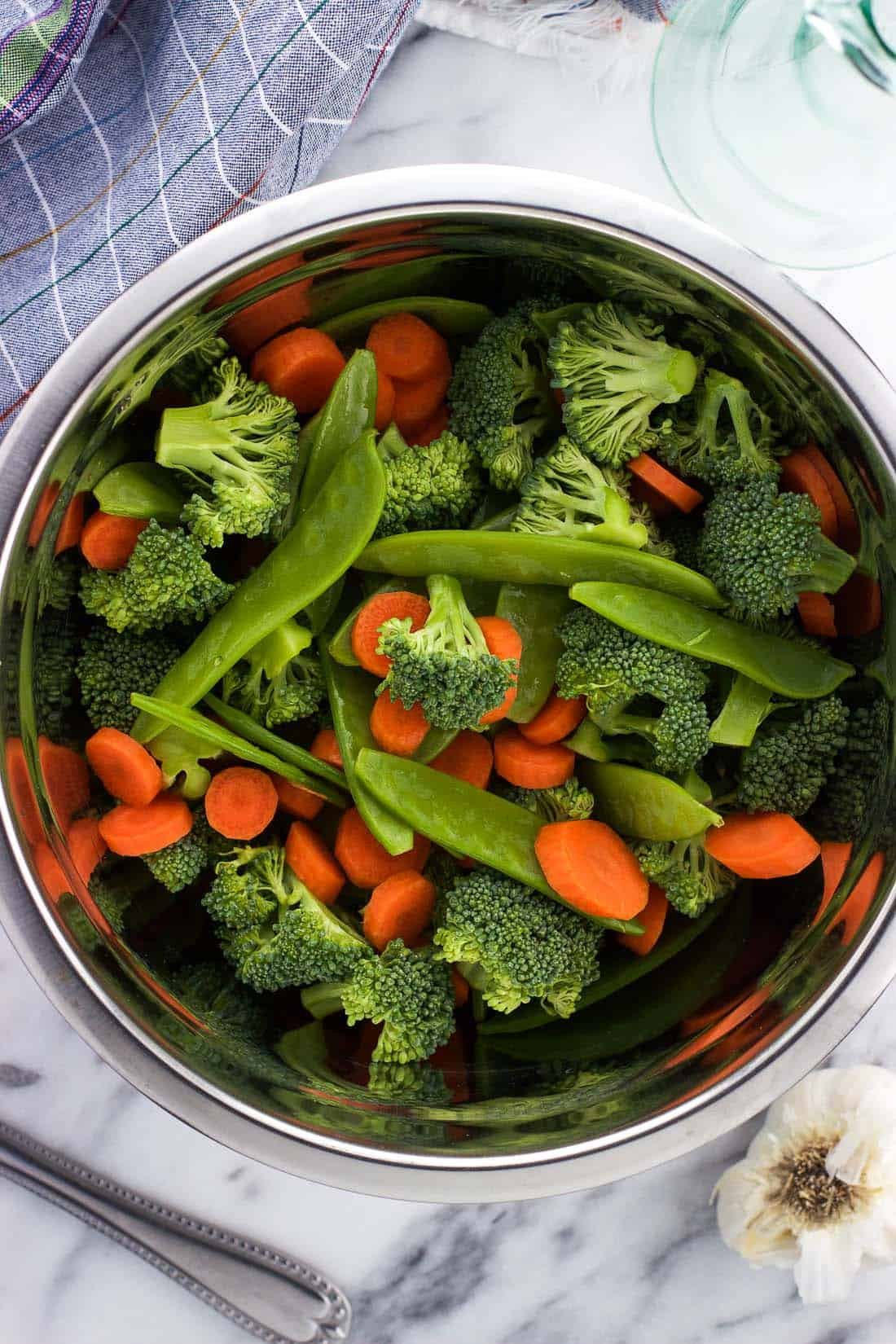 Raw broccoli florets, snow peas, and carrot slices in a mixing bowl.