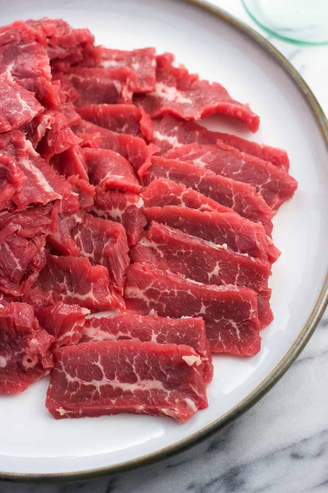 Raw strips of flank steak on a plate before being cooked.