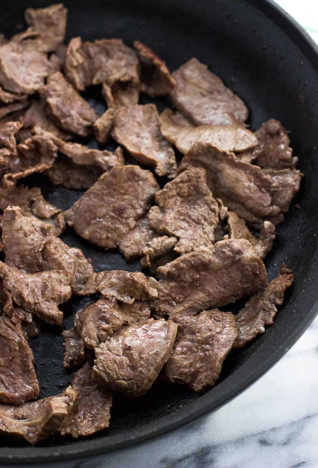 Cooked flank steak strips in a skillet