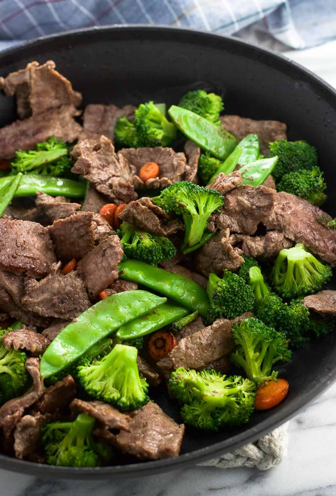 Cooked flank steak strips, broccoli florets, snow peas, and carrots in a skillet.