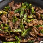 Beef stir fry and mixed vegetables in a skillet with sauce.
