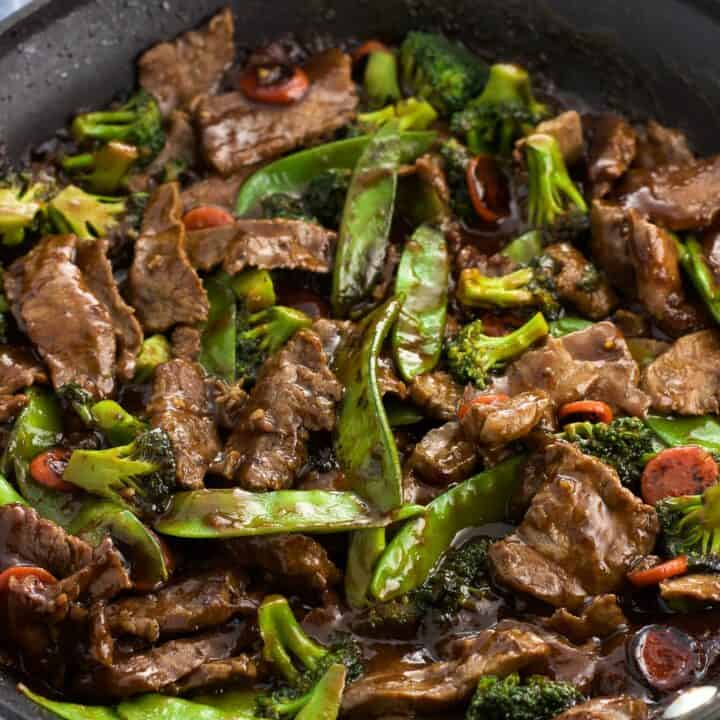 Beef strips and mixed vegetables covered in a balsamic peanut sauce in a skillet ready to serve