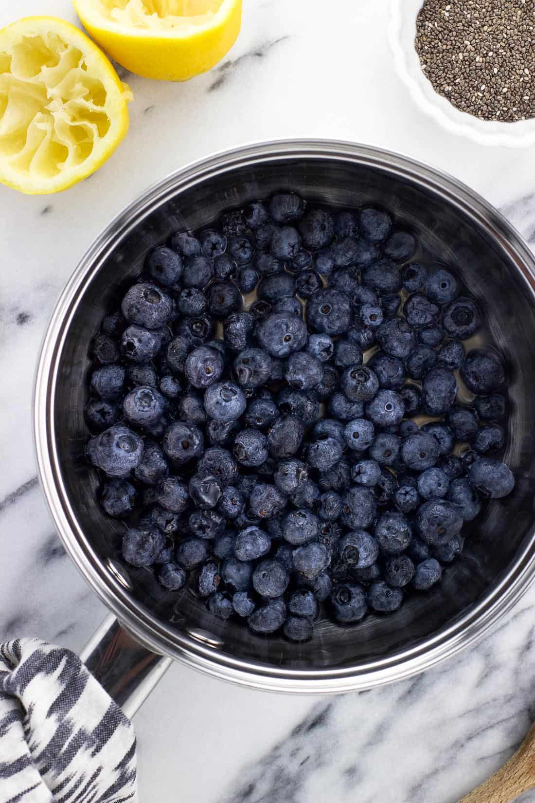 An overhead shot of a medium saucepan filled with fresh blueberries and lemon juice before heating
