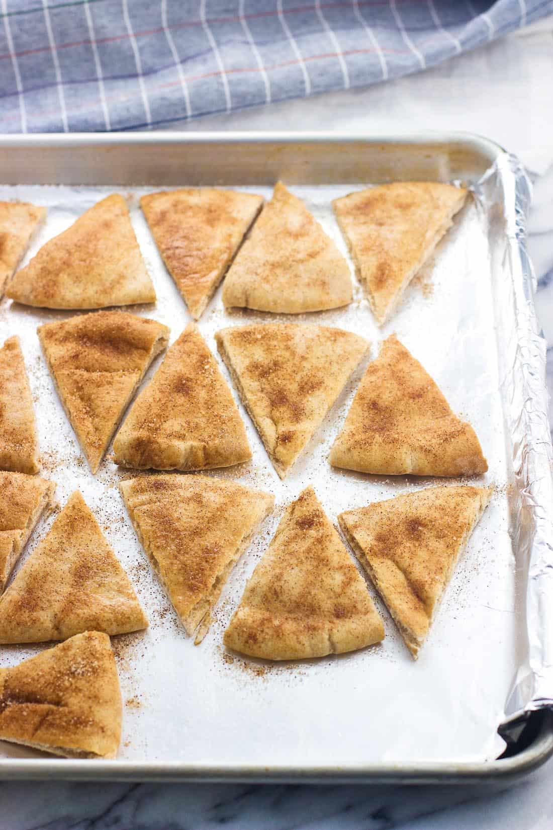 Sliced pita chips on a foil-lined baking sheet pre-bake