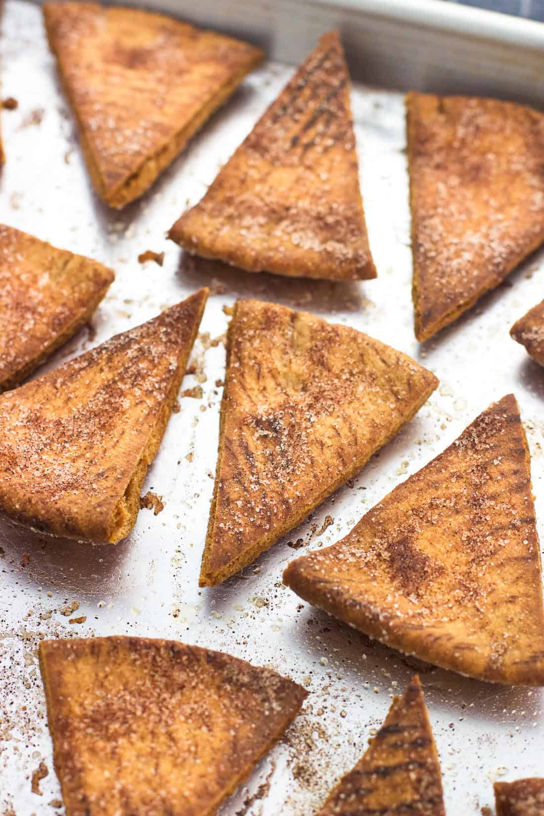 Baked cinnamon sugar pita chips on a foil-lined baking sheet