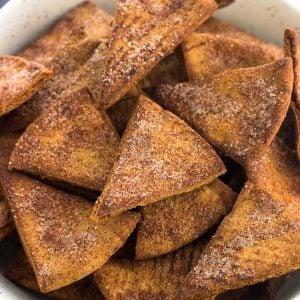 Cinnamon sugar pita chips in a ceramic bowl next to a dish towel
