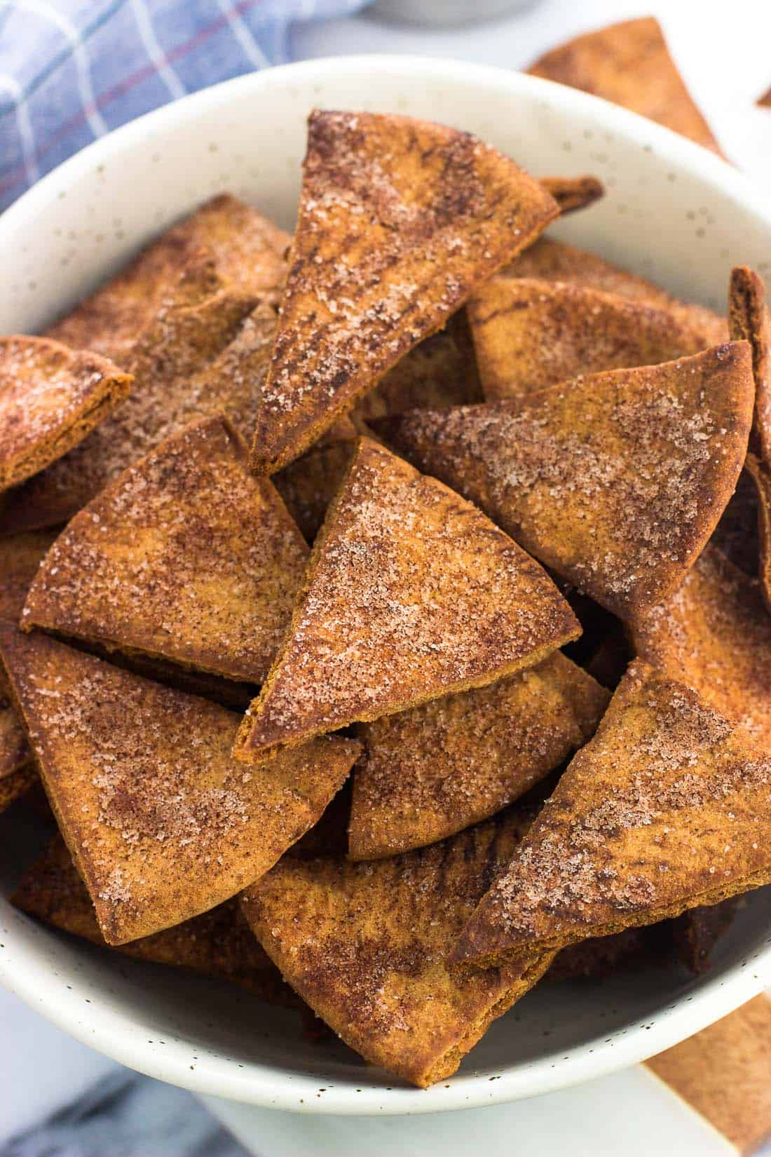 Cinnamon sugar pita chips in a ceramic bowl next to a dish towel