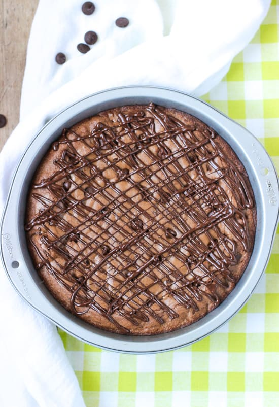 An overhead view of a chocolate-drizzled brownie cake in a metal cake pan.
