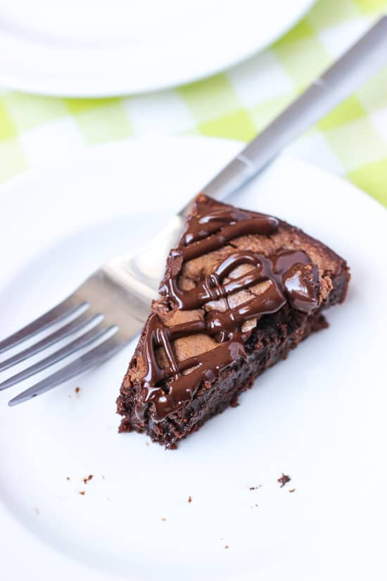 A slice of brownie cake on a dessert plate with a fork.
