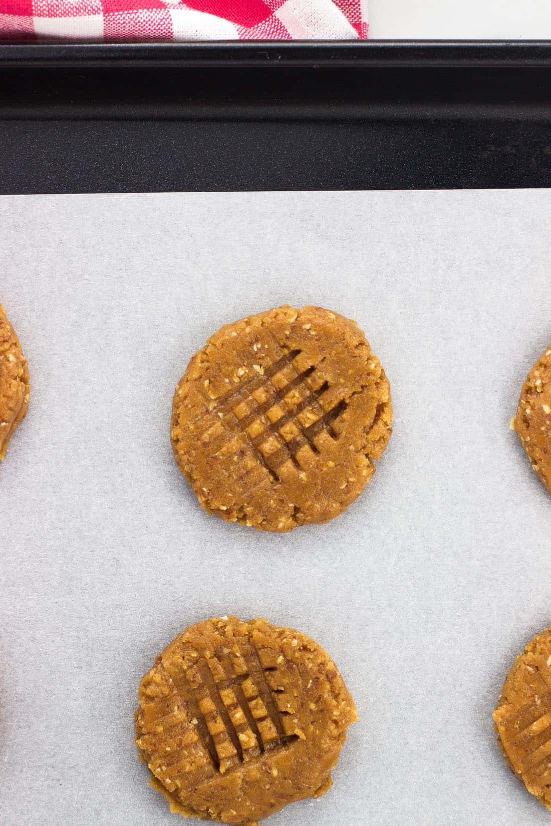Flatted cookies on a baking sheet with a criss-cross pattern pressed on top.