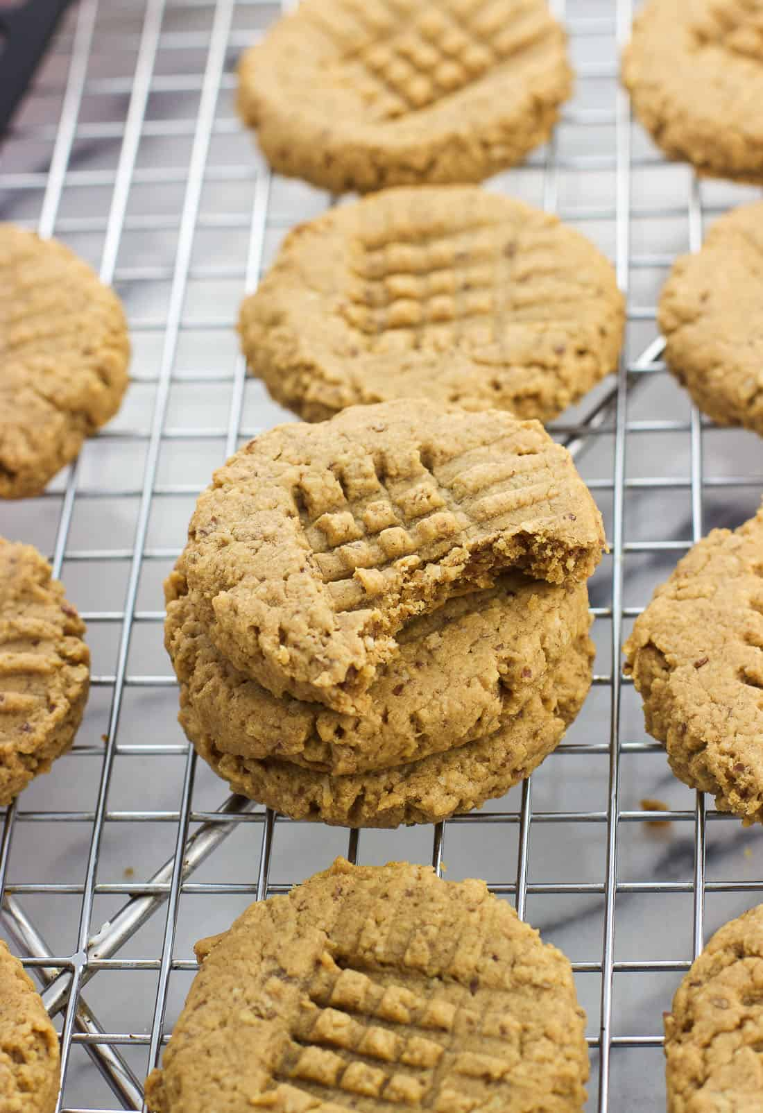 A stack of peanut butter cookies on a wire rack with a bite taken out of the top cookie.