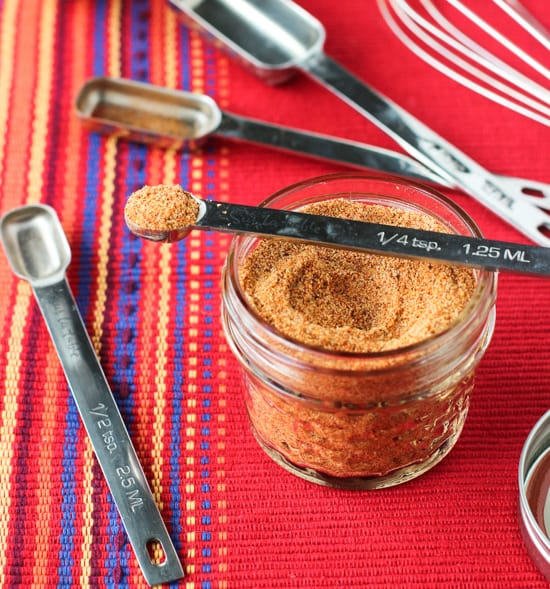 A small glass jar filled with spice mix, surrounded by measuring spoons, with a quarter teaspoon resting on top of the jar filled with a heaping amount of spice