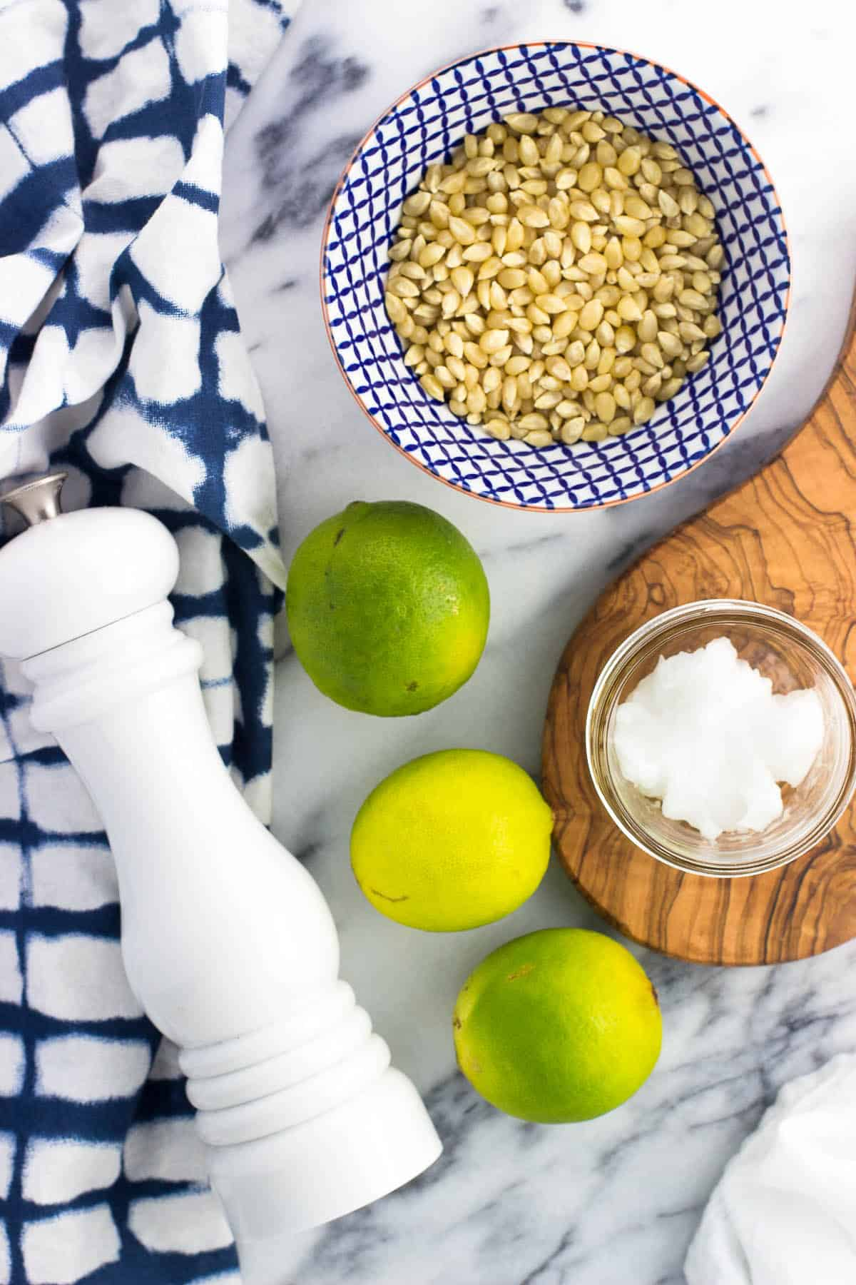 Three limes, a salt mill, a bowl of popcorn kernels, and a small glass jar of coconut oil on a marble board