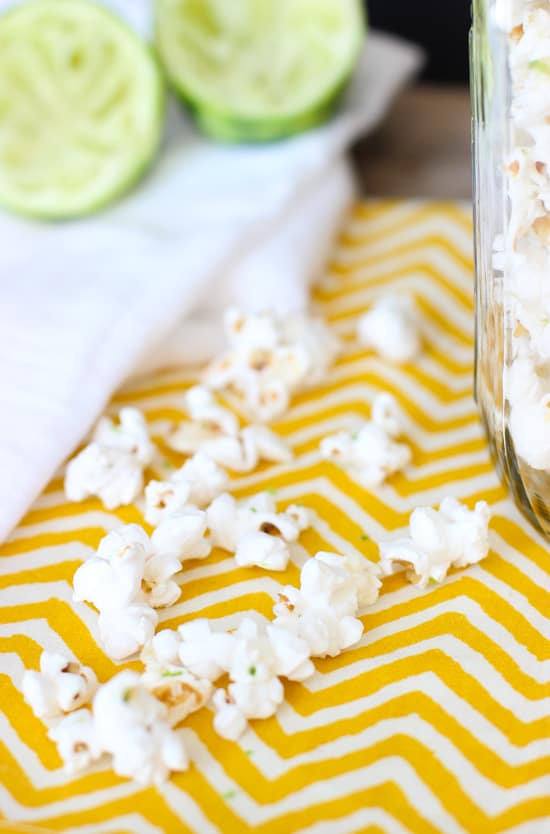 A close-up of popped popcorn kernels on a dishtowel flecked with lime zest