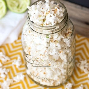 A clear glass jar overflowing with popcorn