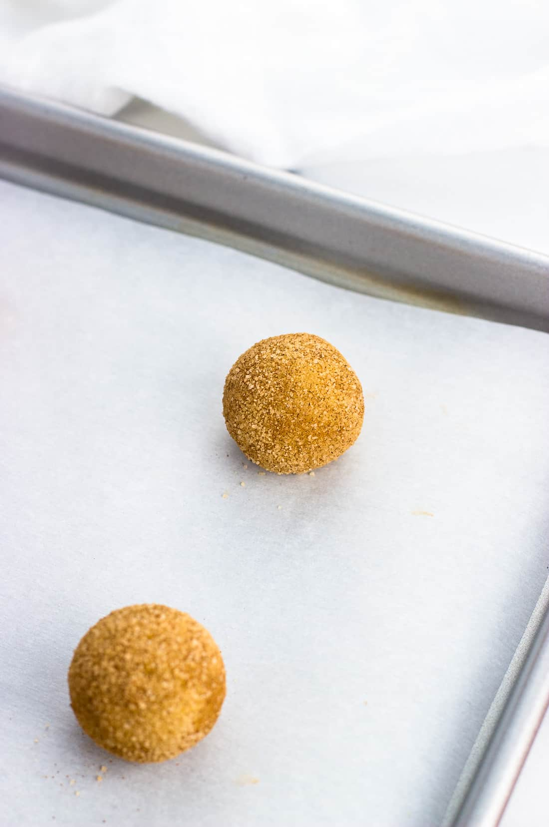 A ball of snickerdoodle dough rolled in cinnamon sugar and placed on a parchment-lined baking sheet, pre-bake
