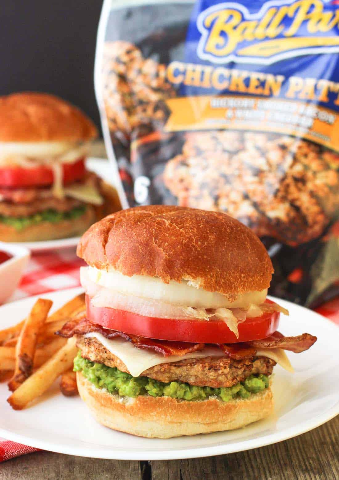A burger loaded with all the fixings on a plate in front of the Ball Park chicken patty packaging
