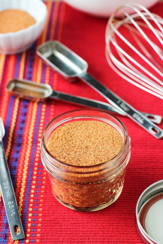 A small glass jar filled with the buffalo seasoning on a cloth placemat, surrounded by a whisk and measuring spoons