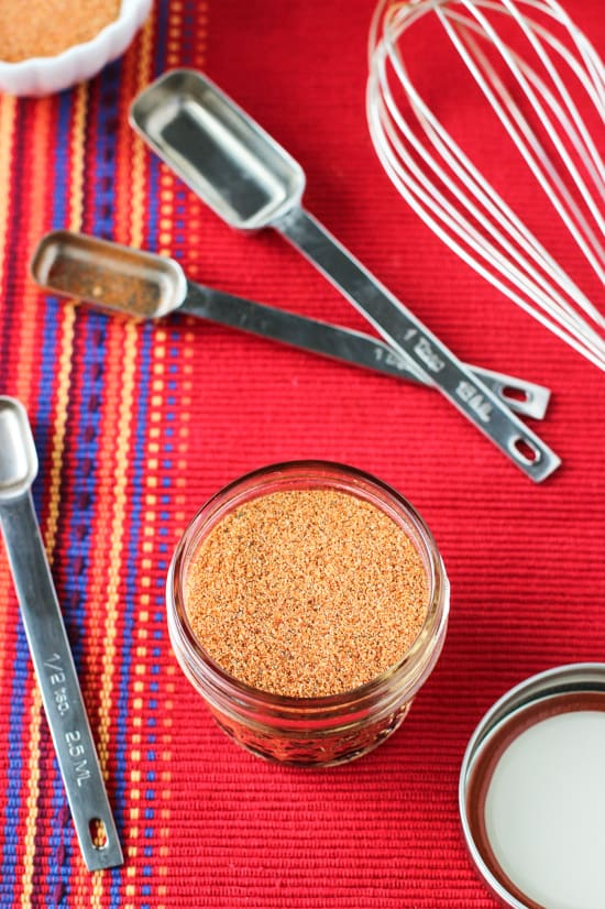 An overhead shot of the jar of spice mix on a cloth placemat