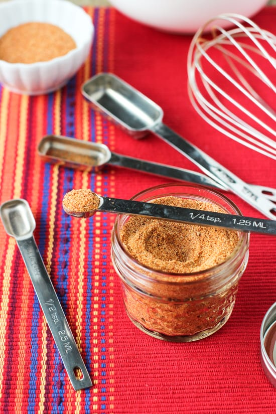 A small glass jar of buffalo spice blend with various measuring spoons.
