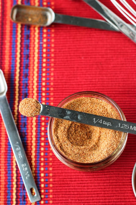A close up of the metal quarter-teaspoon measuring spoon filled with mix resting on top of the glass jar of seasoning