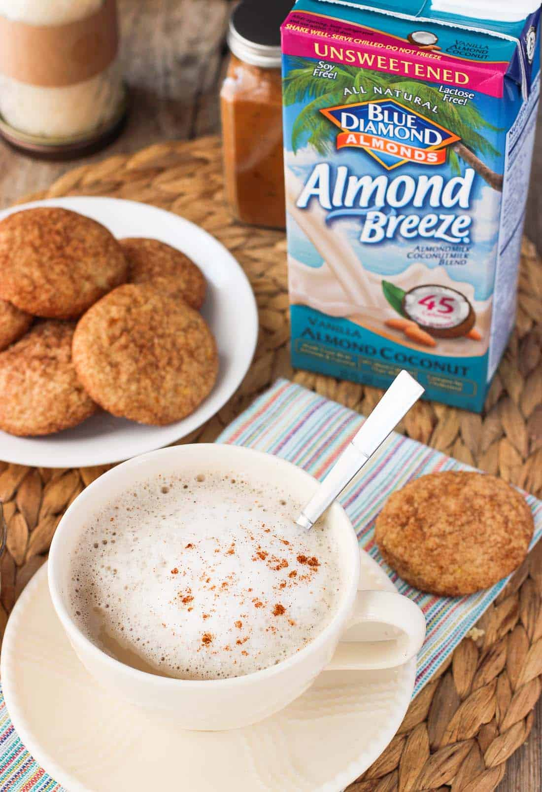 A latte in a mug with foamed milk and cinnamon served next to a plate of cookies with the Almondbreeze container in the background