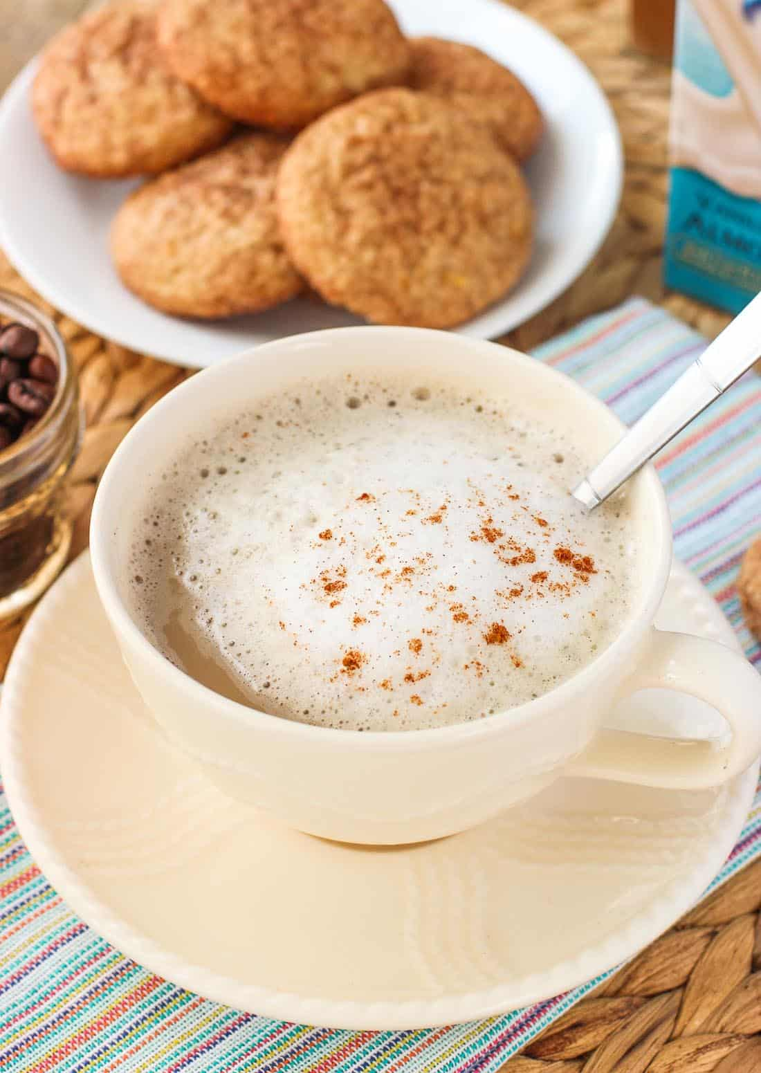 A latte in a wide mug with foamed milk and cinnamon to garnish. In the background is a plate of snickerdoodle cookies