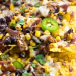 A close-up picture of pulled pork nachos on a sheet pan