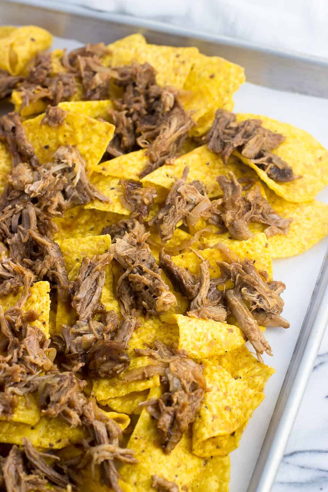 Tortilla chips laid out on a sheet pan topped with cooked pulled pork
