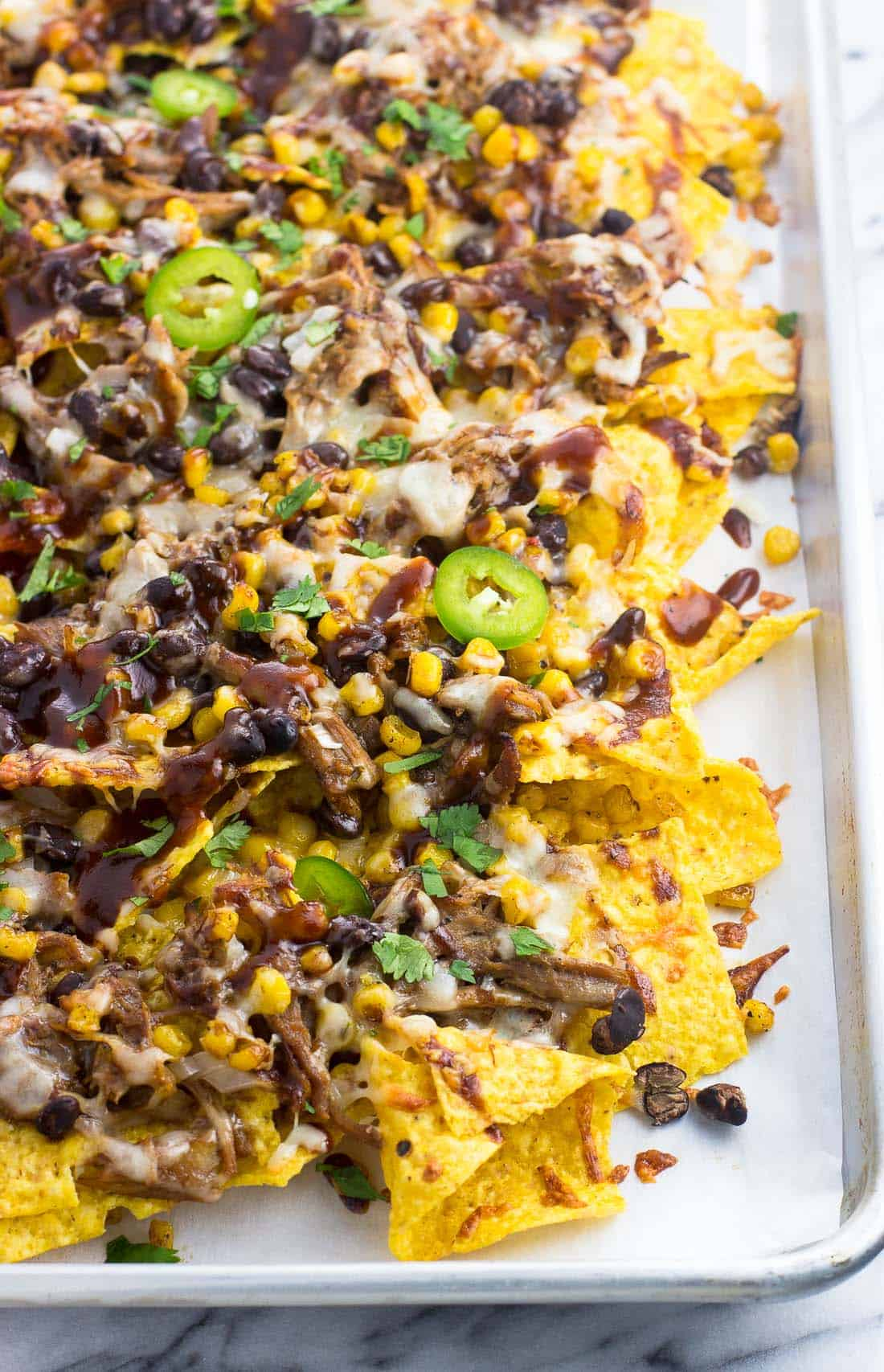 Baked BBQ pulled pork nachos on a tray topped with jalapeno slices