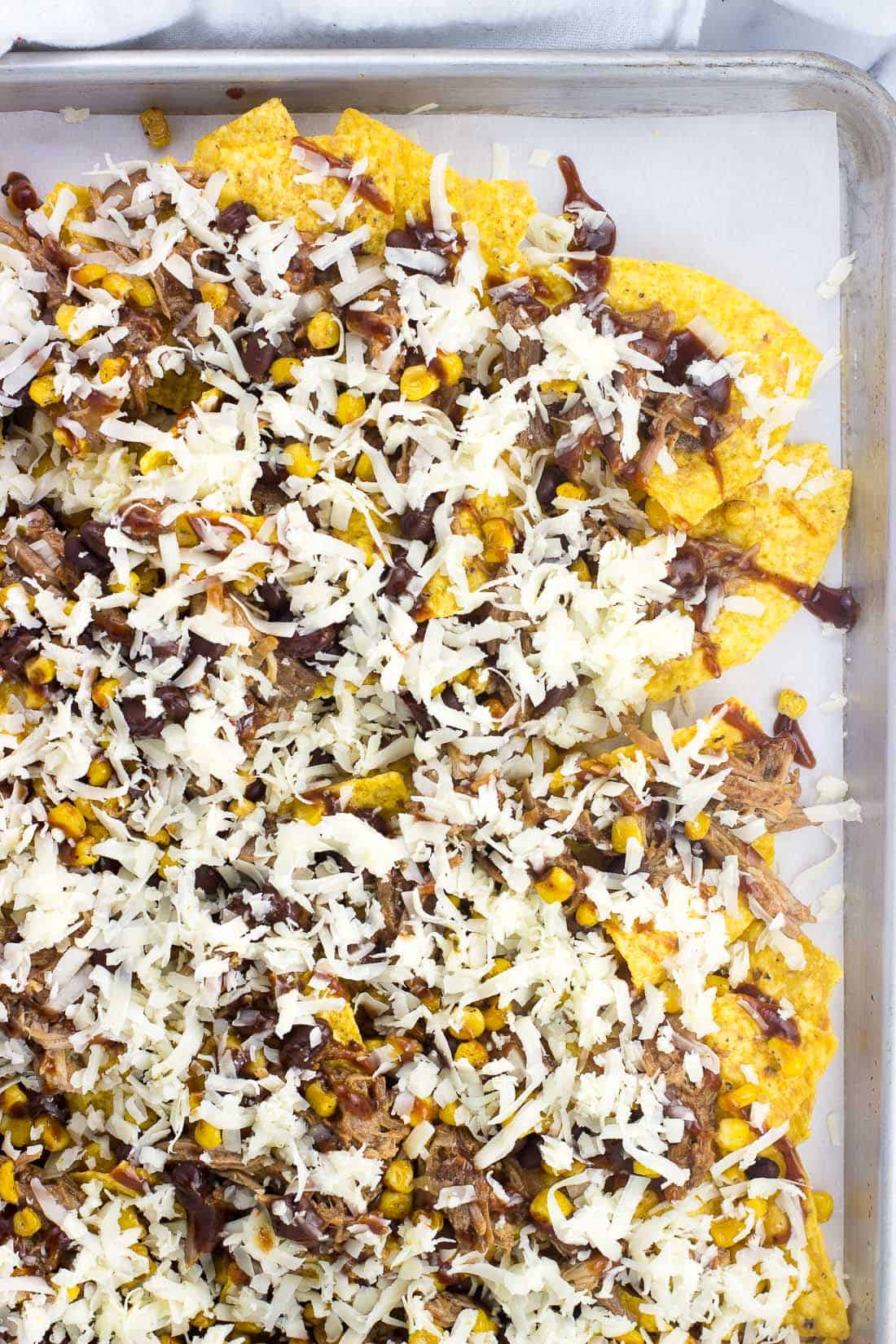 Tortilla chips, pulled pork, corn, and black beans on a sheet pan topped with shredded cheese before going in the oven
