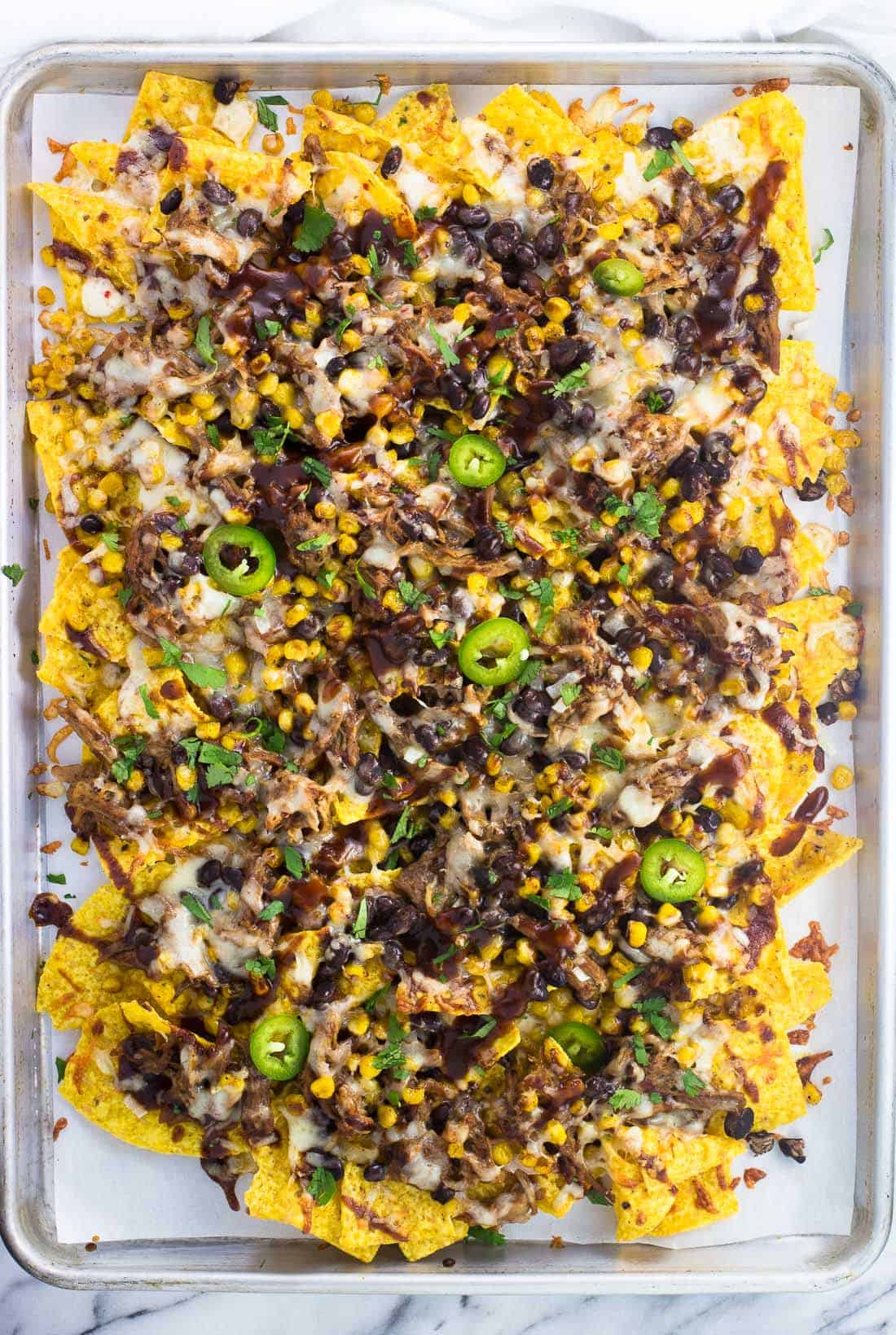 A sheet pan full of pulled pork nachos ready to serve