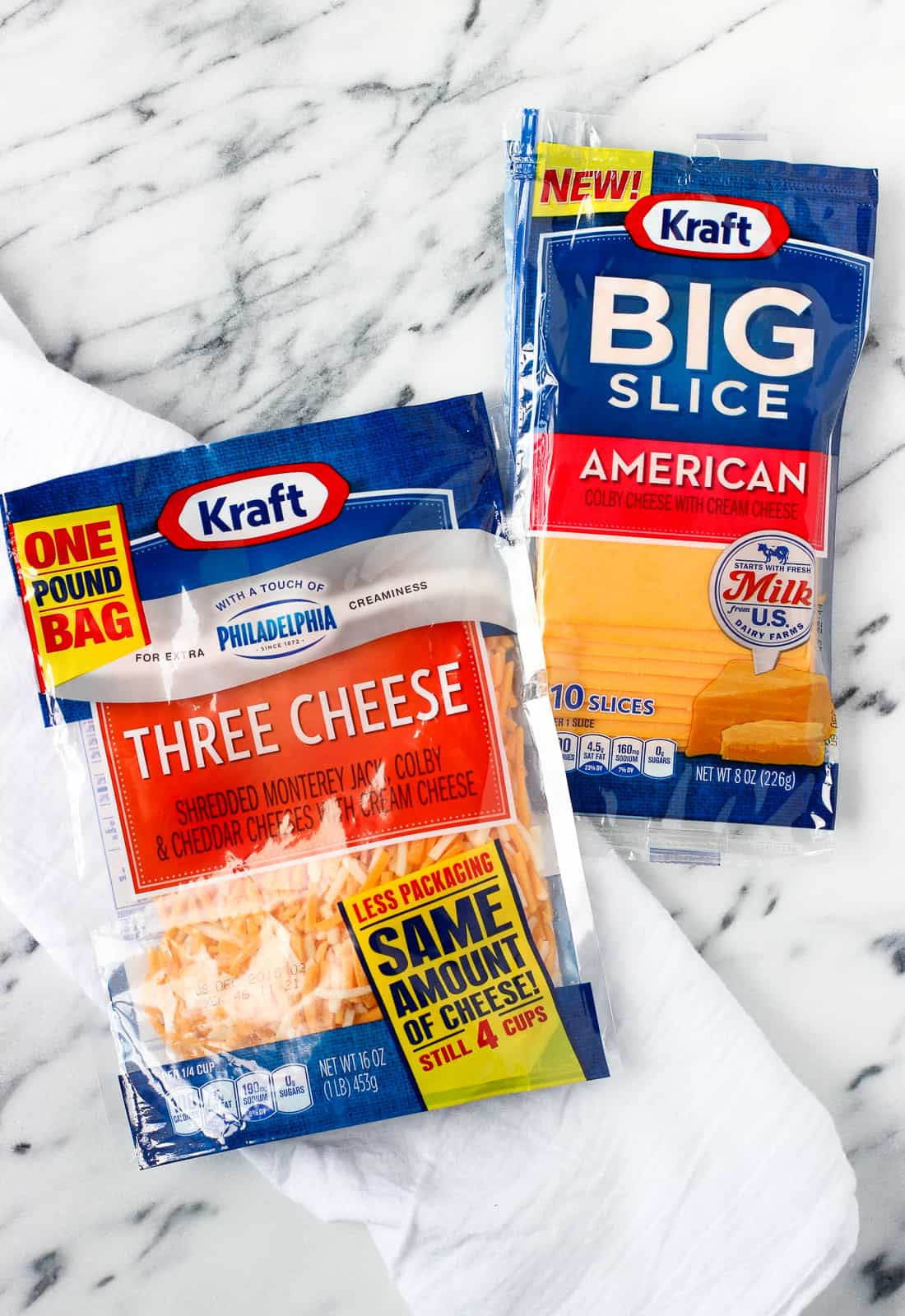 Two cheese packages, one shredded and one sliced, on a marble board.