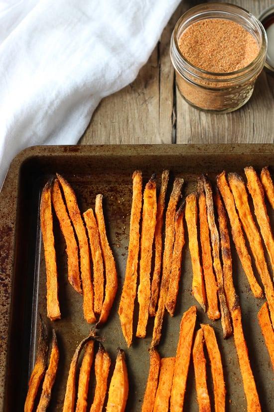 Lined up seasoned sweet potato fries on a baking sheet.