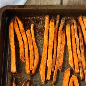 Baked sweet potato fries lined up on a metal sheet pan.