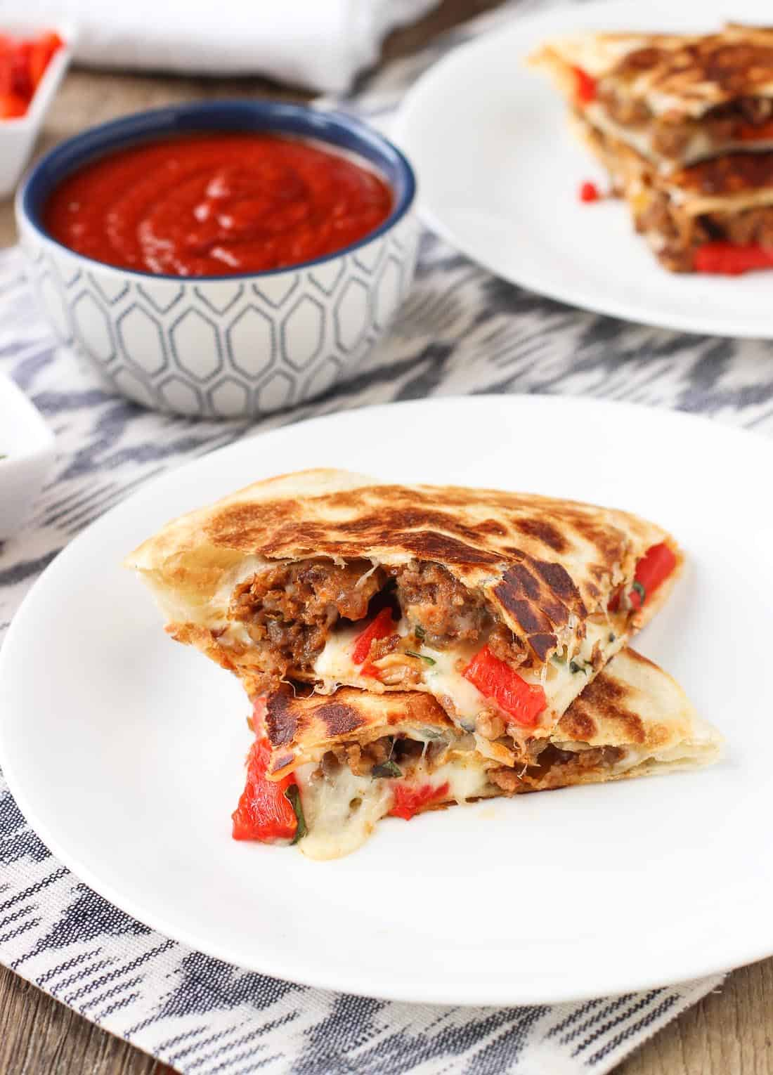 Stacked Italian sausage quesadillas on two plates with a dipping bowl of marinara sauce.