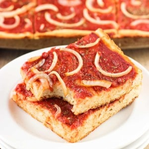 Two slices of focaccia pizza stacked on top of one another on a plate.