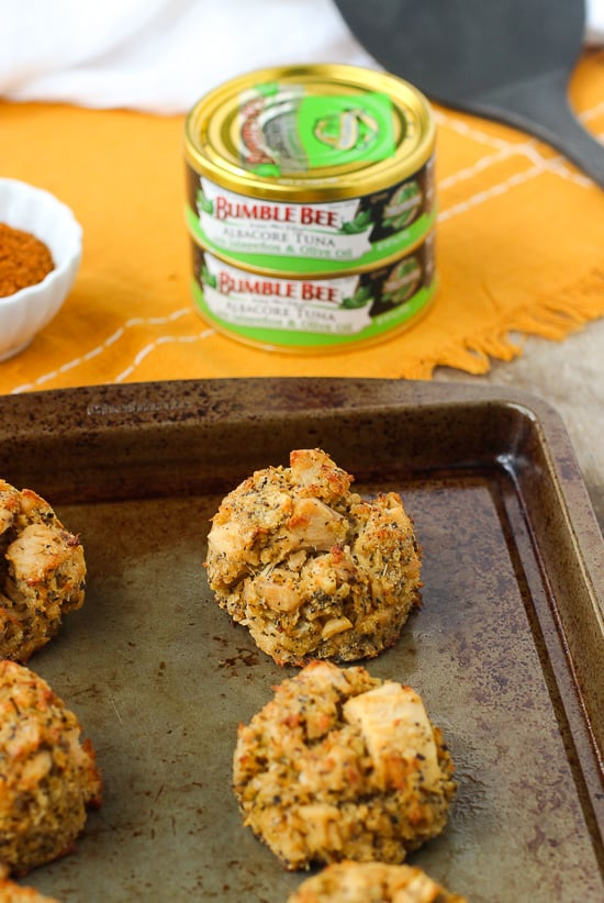Tuna cakes on a metal baking sheet in front of cans of Bumble Bee tuna.