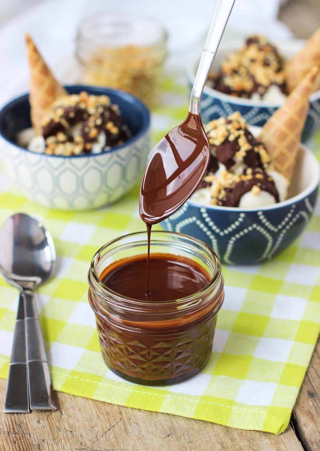A spoon lifted out of a glass jar of chocolate magic shell, showing the thin mixture drizzling off the spoon