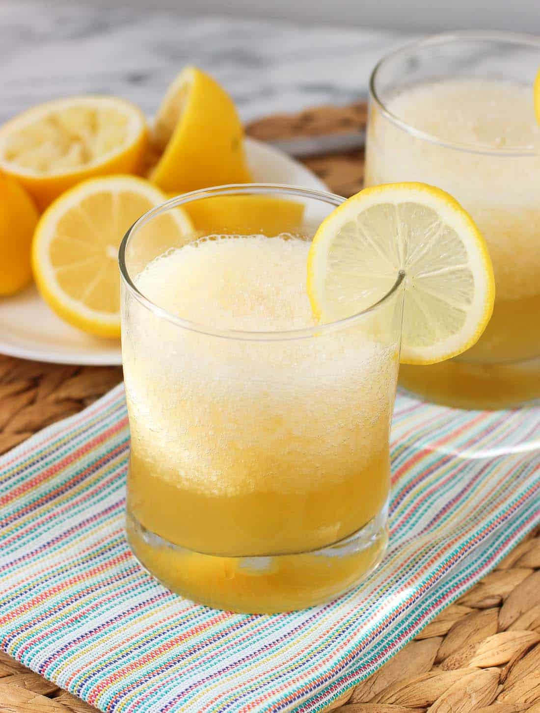 A gold rush cocktail with crushed ice in a short glass garnished with a lemon round with extra lemons in the background