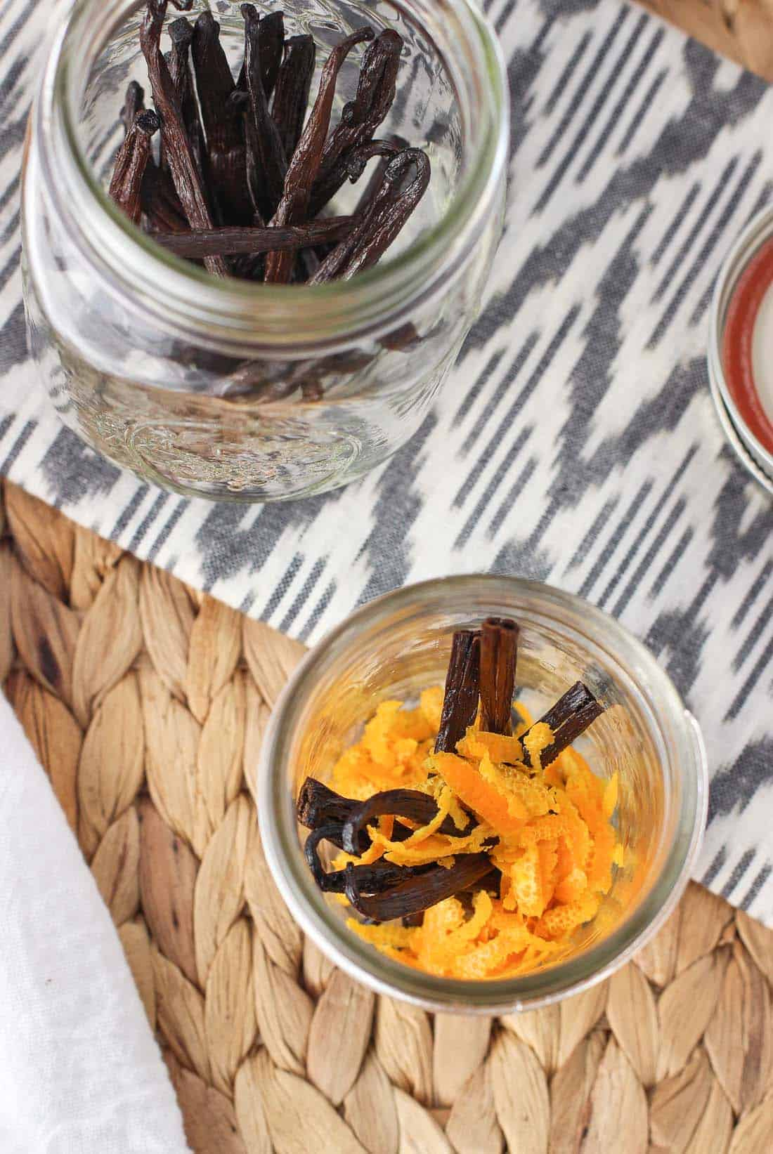 Vanilla beans and grated orange rind in a glass jar.