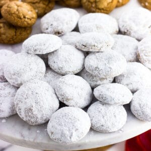 A pile of powdered sugar-coated pfeffernusse cookies on a marble cake stand.